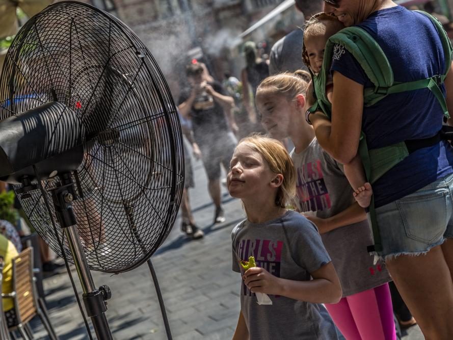 Young family refreshes itself at a fan in the city